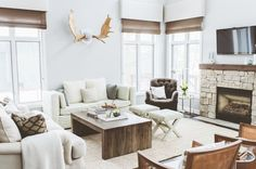 Beach style family room full of nature inspired elements – moose antlers, fantastic wood accents, a stone fireplace, and soft, earthy colors.