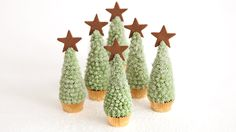 """Serve this snowy dessert this holiday season. Cupcakes are shaped like trees, covered with Snowy Frosting, and sprinkled with sanding sugar. Save some sugar to create beds of """"snow"""" for serving. If you like, you can also make mini gingerbread stars to decorate the tops of the trees."""
