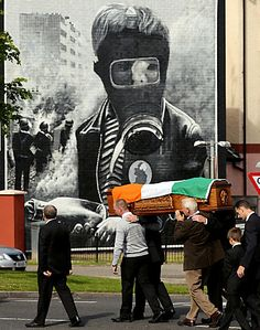 A funeral cortege passes a mural in the Bogside area of Londonderry,