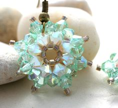 """Light green and opal crystals are hand-woven to make these sea urchin shaped earrings. The crystals are super sparkly and have flashes of yellow and green. The earrings measure about 1.5"""" long and about 1"""" across via Etsy"""