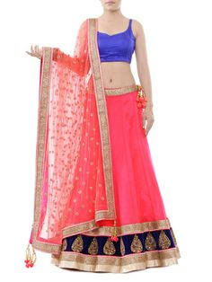 Neon pink net lehenga with intricate gilded embroidery on royal blue velvet border and studs embellished panels. Teamed with royal blue velvet unstitched heavy beaded blouse with exemplary neck and elegant net dupatta with matching border and tassels.