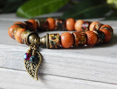 Popular boho leaf bracelet made Robles Wood and a Matte Ceramic Autumn Mixed Rondelles it has an antique bronze Leaf Charm with two tiny handmade charms.