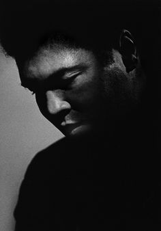 """Ali in New York City, 1984  -  Michael Tighe: """"I shot this photo in 1984 when the world was just starting to learn about his affliction with Parkinson's syndrome. I had shot him 10 years earlier when he was the champ, so it was very difficult seeing him like this, our hero. I shot him a third time in 1999 for Athlete of the Century at his farm in Indiana. When the shoot was over, my assistants and I were invited to have lunch with him and his family at their house. I brought a print of this photo, which I presented to him after lunch. He had never seen it. I handed it to him. He stared at it quietly for a long beat. His eyes watered up, and he handed it back. Everyone got very quiet and uneasy. Then he gestured with the most beautiful smile for me to sign it for him. I got teary-eyed. It is the most cherished moment of my photographer's life."""" Michael Tighe is a portrait photographer."""