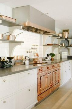 White and gray kitchen with traditional classic white cabinets, concrete countertops, gray and white bracketed open shelving, and a jaw-dropping all-copper stove and double oven. Love!