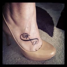 Simple infinity symbol tattoo on woman's foot. There are also initials of her's kids names.