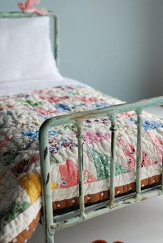 Old bed frame, patchwork quilt, and stuffed bird perched at the head.