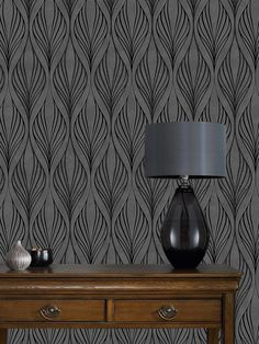 Graham & Brown Optimum Wallpaper – Black/Silver Taking inspiration from the classic art deco designs of the Early 20th Century, the geometric arrangements of this wallpaper are perfect for bringing a your room a stunning air of elegance. On a deep silver background, black patterns subtle touches of glistening glitter and mica highlights create a dramatic feature wall. This wallpaper is available in a range of other colours, so you can match to your décor: - Cream (see item number KC39P)…