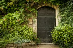 This home's vine-covered wall and muted green door make it fit to be hidden in a secret garden.   - HouseBeautiful.com