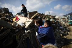 JAPAN-QUAKE/A family looks for their belongings amongst the debris of their destroyed house in Rikuzentakata, Iwate prefecture, where the earthquake and tsunami hit last week, March 18, 2011.