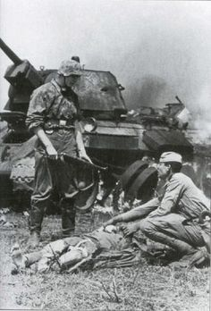 SS soldier watching as a Soviet prisoner helps his wounded comrade. July 1943.