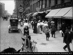 Main Street in the Reynolds Arcade, just east of the Four Corners. Pedestrians are strolling on the sidewalk, and automobiles and bicycles are parked along the curb. Businesses shown are the Western Union Telegraph Cable Office at 15 W. Main, and Straus Bros. clothiers at 16 W. Main. According to an article published with the photograph, records kept by the City Engineer's Department show that 65,791 pedestrians pass through the Four Corners daily.