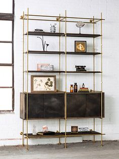 """2 Bay System with Credenza 3'-6"""" and 6'-6"""" shelves, 36"""" shelves with hooks Two - 39"""" Wide Credenzas with patinated Sliding Doors Shelves and Credenza in oxidized Oak, Framework in solid brass with a warm finish. Bay Widths: (Center to Center) 36"""" Size: 6'6"""" W x 22"""" D x 6'-6"""" High"""