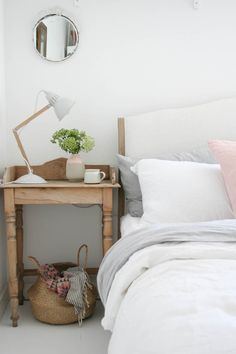 Bedroom makeover with white floors, white linens, pink accents and natural wood | Apartment Apothecary