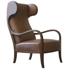 A large, elegant and sculptural 1940s wingback chair with sweeping arms and curved headrests. Frame of Cuban mahogany. Upholstered in Nigerian goatskin.
