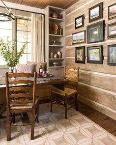 In the cabin's dining room, an assortment of pewter adds patina to the space. The gallery wall is full of nature-inspired paintings. Colorful floor coverings add warmth throughout the home.