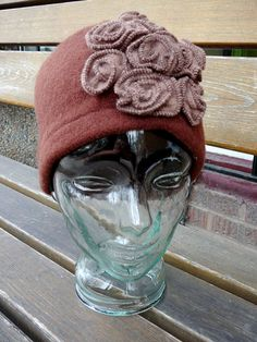 100% felted wool hat with rosettes. Ethically made in China, seen here in brown.