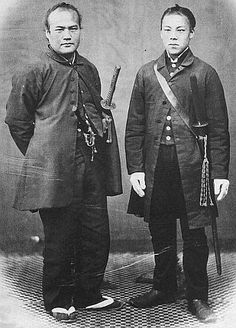 Two samurai wearing western style clothing, both have shoulder carried sword belts.