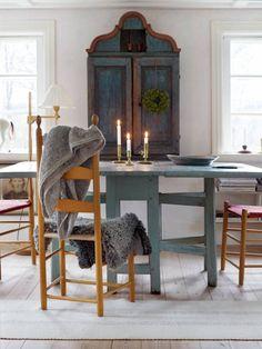 """I köket finns tre av parets antika träskåp. Det minsta hänger på väggen ovanför marmorbänken, daterat 1834. Den dekorativa målningen i blått och rött är härligt nött. """"Att vi är speciellt förtjusta i träskåp beror på att de är vackra, samtidigt som de fyller en funktion."""" På väggen hänger ett altarskåp från Dalsland. Rummet tapetserades först med en mönstrad tapet men det blev för brokigt. Efter ett lager limfärg kändes det mer harmoniskt."""