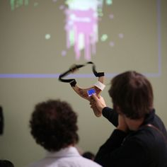 the sms slingshot allows users to digitally send text messages onto urban facades through a slingshot-like device. Interactive Walls, Interactive Media, 3d Printed Heart, Offensive Words, Slingshot, Upcoming Events, Augmented Reality, Geometric Designs, Games For Kids