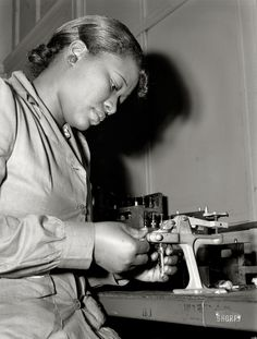 """July 1942. Back at the Melrose Park Buick plant near Chicago. """"Production of aircraft engines. Reconditioning used spark plugs for use in testing airplane motors, Mighnon Gunn operates this small testing machine with speed and precision although she was new to the job two months ago."""" Photo by Ann Rosener, Office of War ."""