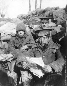 Infantrymen sitting in a trench reading and smoking during the early days of trench warfare in the First World War. (Photo by Keystone/Getty Images)