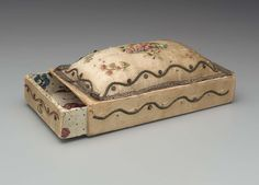 foundation of cardboard box with sliding drawers at each end, ends of drawers, sides of box, and attached pin cushion at top of box covered with white satin (now yellowed and stained), satin embroidered with polychrome silks and gold metal thread and sequins in serpentine border design, arrangement of fruit filled platter in center of pin cushion with fruit or flower spray in each corner, bottom of box and insides of drawers covered with polychrome block printed paper.