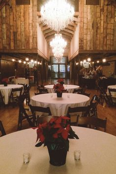 Holiday party setup with candles and poinsettias  #brodiehomestead #holidayparty #holidaypartydecor #partydecor #poinsettias #chandeliers #barnwedding