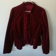 Steampunk Victorian military velvety ruffled Rich velvet-like cranberry red blazer. 73% cotton. 2% spandex 25% rayon. Faux satin-like buttons. Hook & eye closure. Ruffled vertical front and horizontal peplum type ruffles at bottom. Could fit Medium or Large depending on how you want to rock it. Machine washable. Jackets & Coats