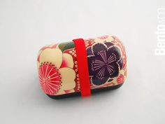 Onigiri Bento Kimono is  a compact bento box with a domed lid. This part is designed to keep onigiri, or Japanese rice balls, upright without crushing them. You could also put small sandwiches or pieces of fruit here. The lower compartment has its own leak-resistant flexible lid, for putting in other foods. A typical onigiri lunch in Japan might have onigiri rice balls with pickled plum filling, with some stewed vegetables, grilled fish and tamagoyaki (a Japanese omelette) in the bottom…