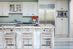This kitchen is really mostly neutral, but the striking pops of aqua (painted floor stripes and backsplash penny tile) draw in the beachy vibe. Design by Tobi Fairley