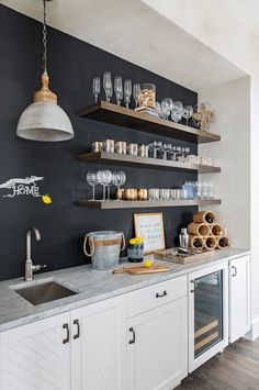 Kitchen Living Rooms Remodeling Stacked stained oak shelves are mounted agains ta black chalkboard wall and over a white and gray marble countertop accenting white plank wet bar cabinets. Wet Bar Basement, Basement Kitchenette, Basement Bar Designs, Kitchenette Ideas, Basement Office, Basement Bathroom, White Bar Cabinet, Modern Bar Cabinet, Wall Bar Cabinet