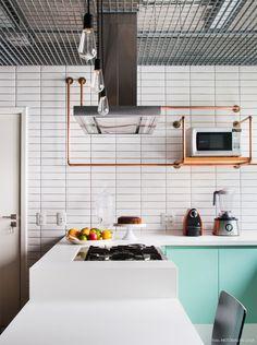 Decoração de cozinha no estilo industrial, com bancada branca e armários azul…