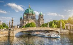 A passenger boat coming out from under the bridge at the front of Berlin Cathedral on a bright sunny day. Hotel Berlin, Berlin City, Budapest, Bangkok, Amsterdam, Dubai, Baltic Cruise, Edinburgh, Athens