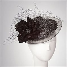 • Veuve Noir  • Design by Jill Courtemanche  • Colors: Black  • Size: Fits Most  • A bit cocky and a bit cute, this cunning cocktail hat of black vintage racello straw is edged in horsehair and trimmed with black veiling, feather flower, and velvet leaves. Lined in silk and perfect for soft summer evenings. One size fits all.