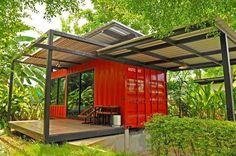 werfen sie einen blick auf diese idee für ein container haus   hier ist ein kleines rotes landhaus mit terrasse und sofas und einem garten mit grünen pflanzen und bäumen