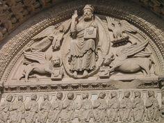 """Les symboles des quatre Évangélistes entourant le Christ en majesté - Tympan de la cathédrale Saint-Trophime d'Arles - Le tétramorphe, ou les """"quatre êtres vivants"""", représente les quatre animaux ailés tirant le char de la vision d'Ézéchiel, Livre d'Ézéchiel (1; 1-14). Plus tard, les Pères de l'Église y ont vu l'emblème des quatre Évangélistes : le lion pour Marc, le taureau pour Luc, l'homme pour Matthieu & l'aigle pour Jean. Ils accompagnent souvent les représentations du Christ en gloire."""