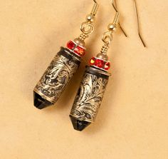 """Etched bullet casing jewelry, earrings """"Wild West"""", are made from shells. We have etched them with an awesome flourish pattern. Topped with a vivid Hibiscus red Swarovski rhinestone and a denim blue Swarovski """"bullet"""". Bullet Casing Jewelry, Wild West, Jewelry Ideas, Shells, Swarovski, Bling, Personalized Items, Earrings, Pattern"""