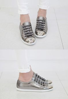 Let out your fun style during the day or at a concert late into the night with these silver tone metallic sneakers. Look totally fab when you wear these with a black neoprene pullover in floral print and flared skater skirt. - Reinforced toe boxes - Embellished laces - Textured sides - Low cut - Color: Silver