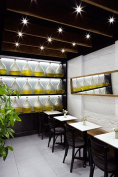 At the back of this modern restaurant is a more formal dining area featuring a wall of oils that adds authenticity to the Greek restaurant and a horizontally placed mirror that helps the small space feel larger and more open.