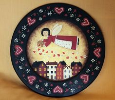 A wooden plate has been hand painted with a primitive style Valentines Day design. A cheerful angel dressed in a bright red dress and wearing a red polka-dotted apron hovers over a small village as she dispenses hearts and daisies from her basket. The rim of the plate is decorated with lots of red hearts and daisies. The plate measures 9 1/2 inches in diameter and has been sealed with matte finish.  PLEASE NOTE: Each plate is individually hand painted to order. The one you receive may vary…