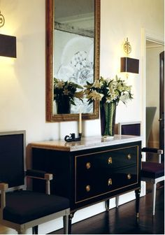Gorgeous black wood marble top chest with gold accents! Love the upholstered black accent chairs flanking the chest and black leather box sconces! black brown gold ivory cream entrance foyer colors. ivory cream paint wall colors!