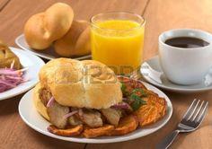 Desayuno peruano conformado con Pan Chicharron (Bun con carne frita) y frito batata, tamal (a la izquierda), salsa criolla (ensalada de cebo...