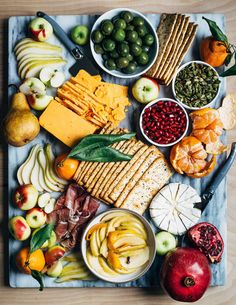 A modern holiday cheese board with red cheddar and brie-style cheeses, winter fruit, and sweet and sour quick-pickled apples, created in partnership with @wholefoodsmarket. #WholeFoodsMarket
