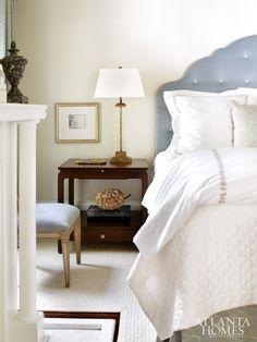 Aqua and cream tones create a serene master bedroom. Custom headboard upholstered in Jim Thompson mohair. Dust skirt, custom, Lee Jofa. Bed linens from Gramercy Home. Hickory Chair bench upholstered in Pierre Frey velvet stripr. Wool-and-sisal rug from Eve