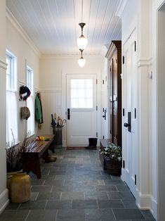 An oversize mudroom for this New England farmhouse custom design. Dutch doors, beadboard on the walls and ceiling, Vermont slate tile flooring, schoolhouse lights and a sturdy bench for taking boots off. New England Farmhouse, Home, Slate Flooring, School House Lighting, House Design, Remodel, New Homes, Mudroom, Entry Hall