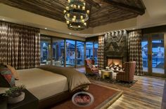 Rustic Luxury Bedroom With Glass French Door, Pair Of Wingback Chairs Near Fire Place And Adorable Chandelier