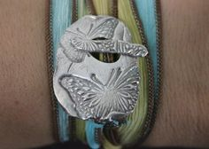 This sweet toggle, with beautiful dragonflies, is hand crafted from reclaimed silver. Shimmering in the summer sun, this dragonfly toggle is interlaced with a hand dyed silk ribbon with cool hues like the rainforest that wraps end over end around your wrist. The gentle sari wrap is generous, and flowing in grace and comfort just like a carefree summer day. The artisan toggle ornament, with this joyful dragonfly is crafted from pure, fine, environmentally friendly, silver and is 99% pure.