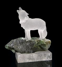 <i></i><i>by Peter Mueller<br />Brazil</i><br />This realistic carving of an arctic white wolf, in rock crystal quartz, shows the animal howling to communicate with its pack. The wolf has yellow eyes and a black obsidian nose. A natural fissure in the quartz highlights the fur of its neck. The wolf stands on a promontory of Brazilian emerald in matrix, which is mounted on a polished rock-crystal plinth slab.<br /><i>Measures 7 ¾ x 6 ¾ x 4 inches; wolf is 5 inches tall </i><br /><i></i>