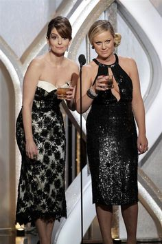 """Co-hosts Tina Fey, left, and Amy Poehler swig a stiff drink after losing out for best actress in a television comedy series to Lena Dunham of """"Girls."""" (Photo: Paul Drinkwater / NBC via AP) #GoldenGlobes"""
