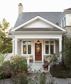 Cedar shingle siding, white trim and a salvaged Victorian door offer a warm welcome to this lovely weekend retreat.